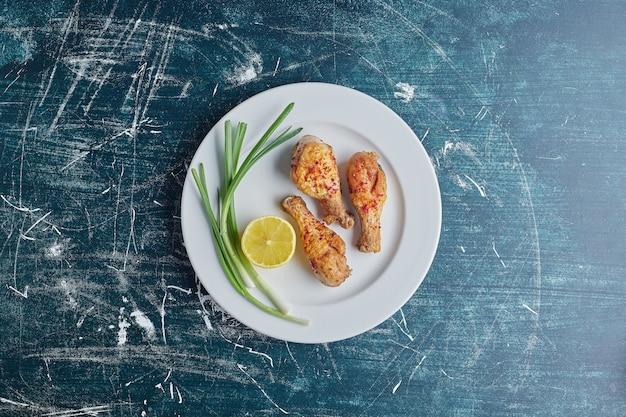 Сырые куриные окорочка с зеленью и лимоном.