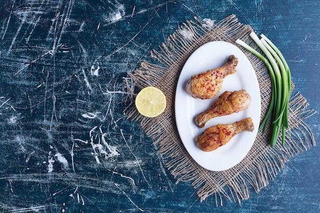 Cosce di pollo crude con vegetazione e limone.