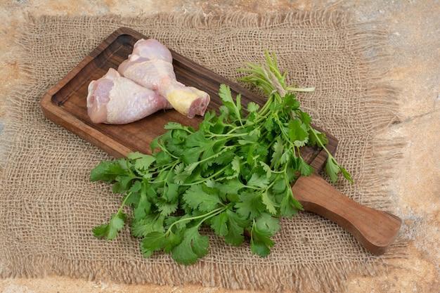 Cosce di pollo crude con verdure sul tagliere di legno su tela di sacco