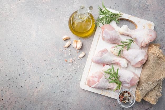 커팅 보드에 허브와 향신료와 함께 원시 닭 다리