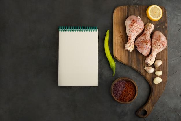 Cosce di pollo crude con un libretto di ricevute da parte
