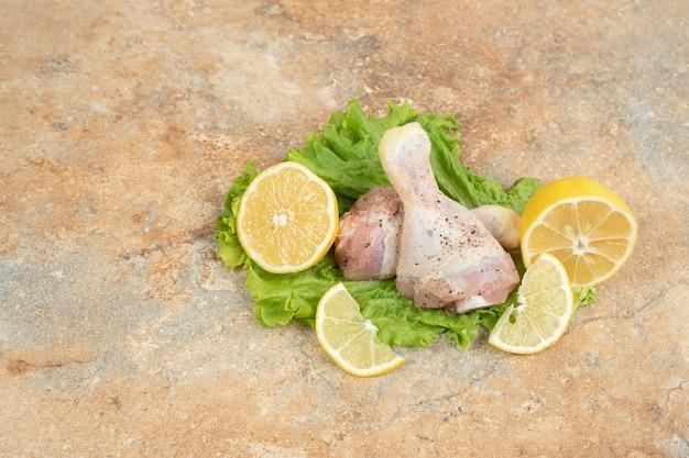 大理石の表面にスライスしたレモンとレタスを添えた生の鶏の脚