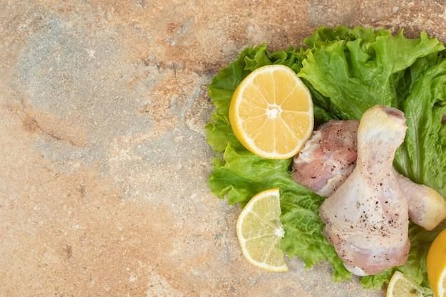 Cosce di pollo crude con fette di limone e lattuga su superficie di marmo