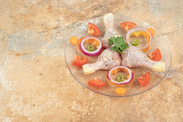 Raw chicken legs with sliced tomato and onion on glass plate