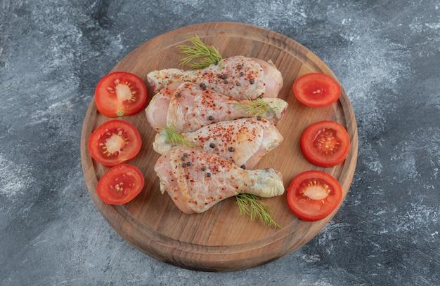 나무도 마 보드에 향신료와 함께 원시 닭 다리. 치킨 카레를 준비 할 준비가되었습니다.