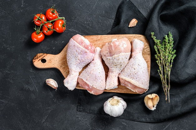 Raw chicken legs with spices and vegetables on a wooden cutting board