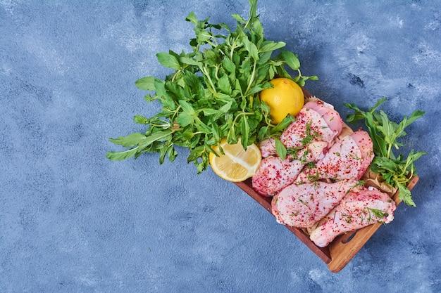 Cosce di pollo crude con spezie su una tavola di legno sul blu