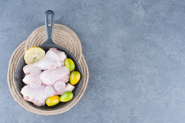 Cosce di pollo crude con verdure in padella nera.