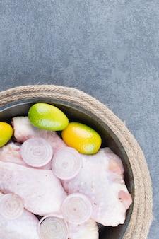 Cosce di pollo crude con verdure su piatto scuro.