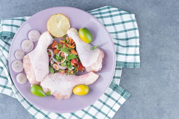 보라색 접시에 야채와 함께 원시 닭 다리입니다.