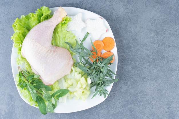 흰색 접시에 야채와 함께 원시 닭 다리입니다.