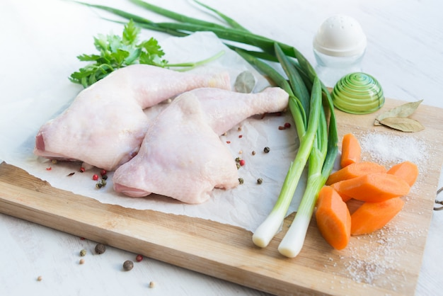 Raw chicken legs with vegetables and spices.