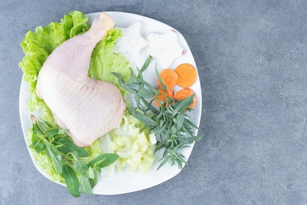Cosce di pollo crude con verdure sul piatto bianco.