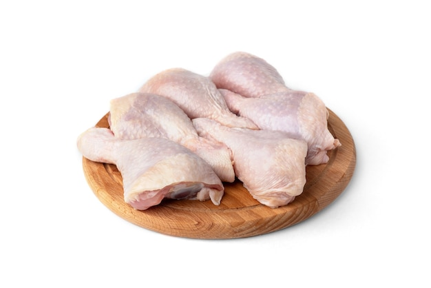 Raw chicken legs on wooden board isolated on white background.