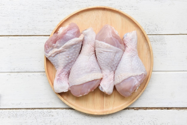 Raw chicken legs on wooden plate / fresh uncooked chicken meat for cooking