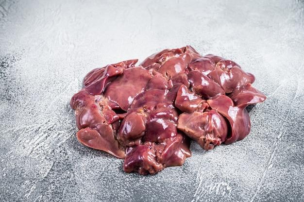 肉屋のテーブルに生の鶏レバー肉。白いテーブル。上面図。