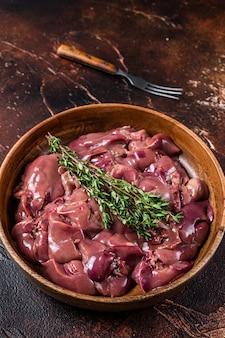 나무 접시에 생 닭 간 찌꺼기. 어두운 배경입니다. 평면도.