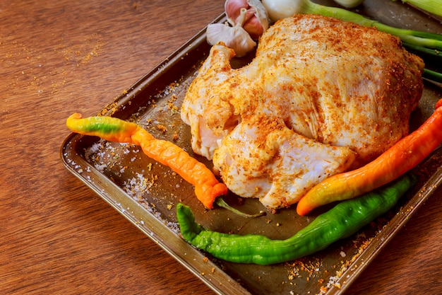 Raw chicken marinated with garlic, herbs, spices close up in a dish for baking.