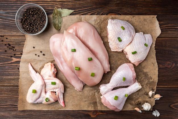 Raw chicken meat on dark wooden table.