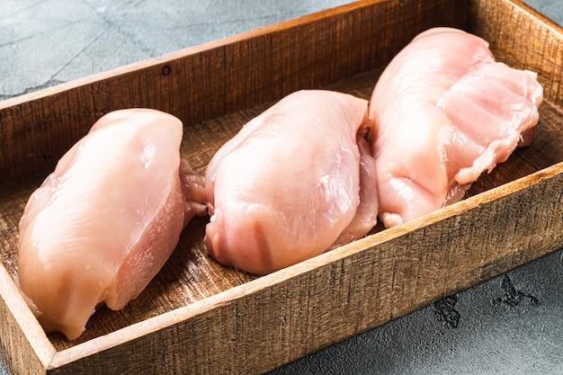 회색 돌 위에 있는 나무 상자에 있는 생 닭고기 필레 세트