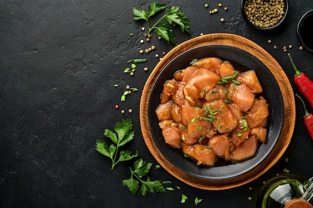 Сырое куриное мясо, маринованное в соевом соусе терияки, луком и перцем на черной тарелке на темной бетонной поверхности