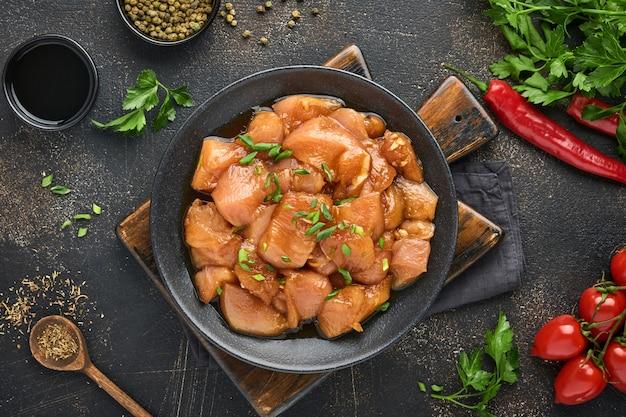 다크 슬레이트, 돌 또는 콘크리트 배경의 검은 접시에 데리야끼 간장, 양파, 후추로 절인 생 닭고기. 복사 공간이 있는 상위 뷰입니다.