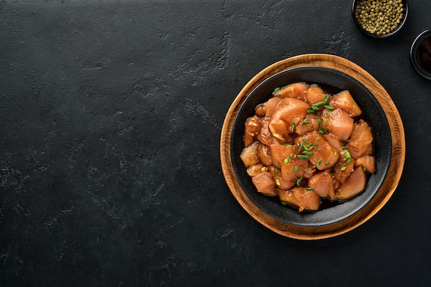 Raw chicken meat marinated in teriyaki soy sauce, onions and pepper in a black plate on a dark concrete surface