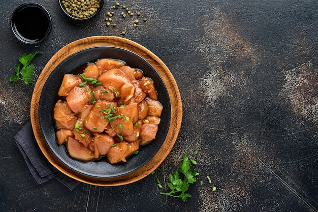 Raw chicken meat marinated in teriyaki soy sauce, onions and pepper in a black plate on a dark slate, stone or concrete background. top view with copy space.