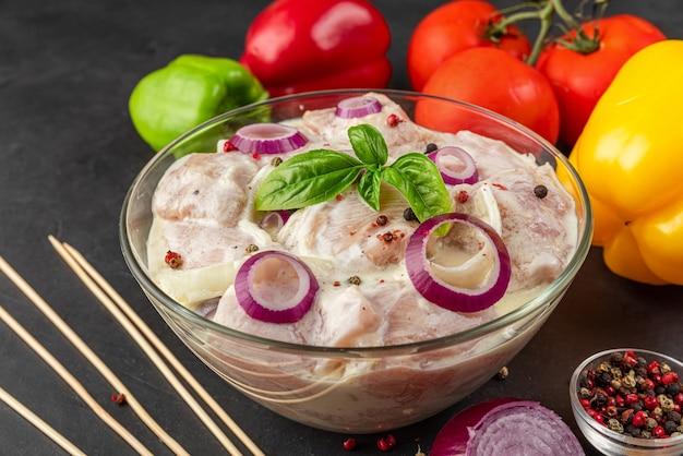 Сырое куриное мясо, замаринованное майонезом или сметанным соусом, перец, лук, базилик в миске на черном фоне. крупным планом. маринование мяса для приготовления шашлыка. закрыть