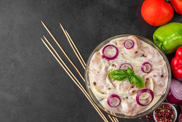 Сырое куриное мясо, замаринованное майонезом или сметанным соусом, перец, лук, базилик в миске на черном фоне. вид сверху