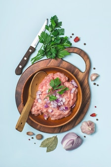 Raw chicken meat mince in a bowl with spices