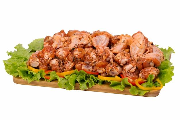 Сырое куриное мясо на разделочной доске на белом фоне.