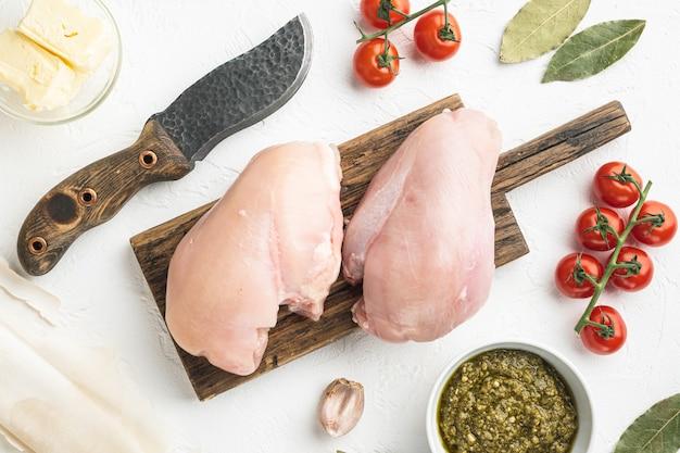 흰 돌 배경에 필로, 허브, 버터 세트가 포함된 생 닭고기 속 재료, 평면도