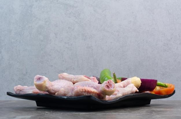 Carne di pollo cruda con peperoni e cipolla su piatto scuro. foto di alta qualità
