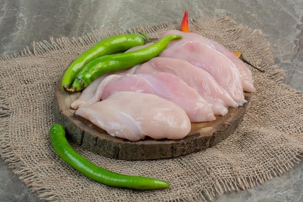 Carne di pollo cruda con peperoni su tavola di legno. foto di alta qualità