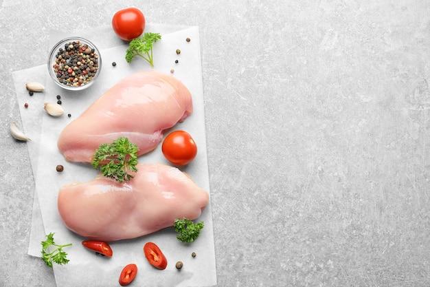 Сырое куриное мясо со специями на сером фоне