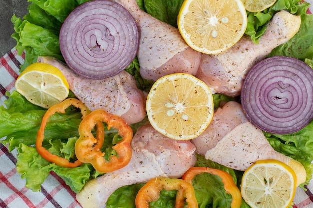 Сырое куриное мясо с овощами и специями на мраморном фоне. фото высокого качества