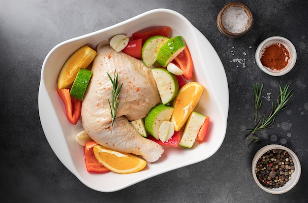Raw chicken meat with vegetables oranges and spices in ceramic pan balanced food
