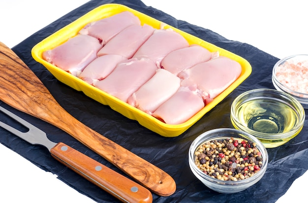 Raw chicken meat in yellow tray.