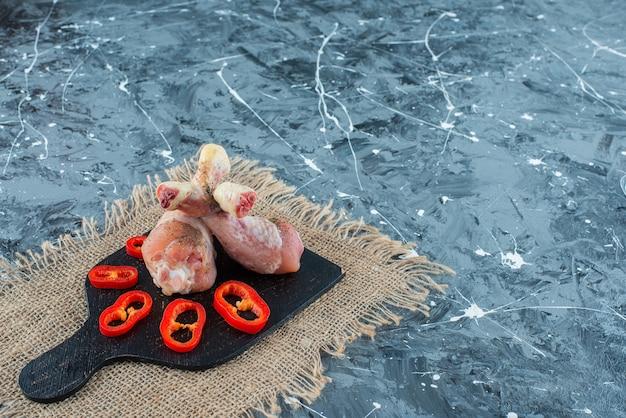 Carni di pollo crude e pepe a fette su un tagliere sulla tela, su sfondo blu.