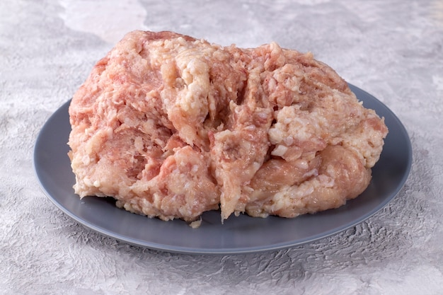 Raw chicken mince on a gray plate on a light background.