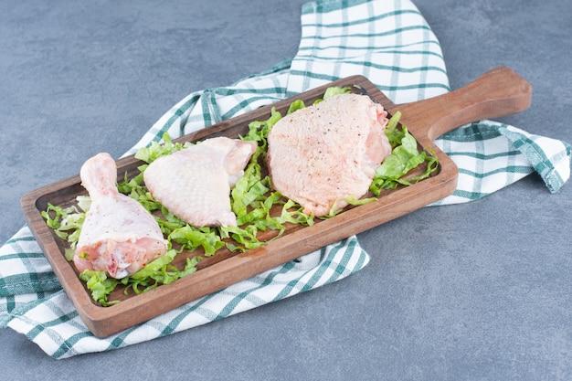 Parti di pollo crudo su tavola di legno. Foto Gratuite