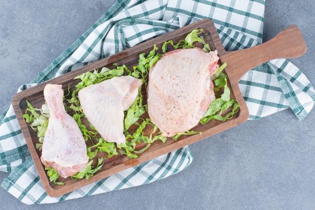 Parti di pollo crudo su tavola di legno.
