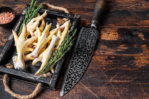 生の鶏の足を肉屋のまな板にナイフで足