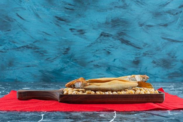 青いテーブルの上の赤いテクスチャーのボード上の生のチキンエンドウ豆とロースト魚。