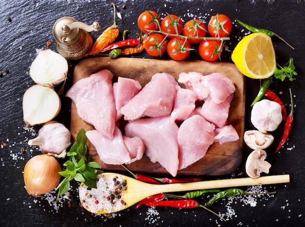 ダークボードに野菜を添えた生の鶏肉