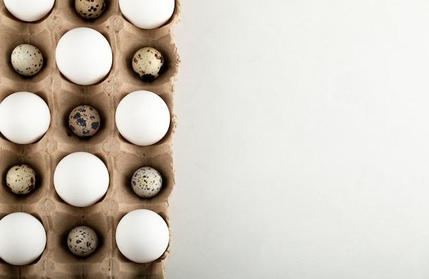 Pollo crudo e uova di quaglia in un contenitore di cartone.