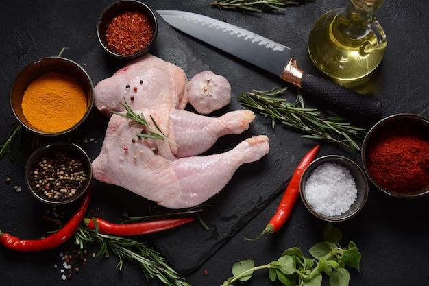 어두운 배경에서 그릴 준비가 된 생 닭 구역, 허브와 향신료가 있는 다리.