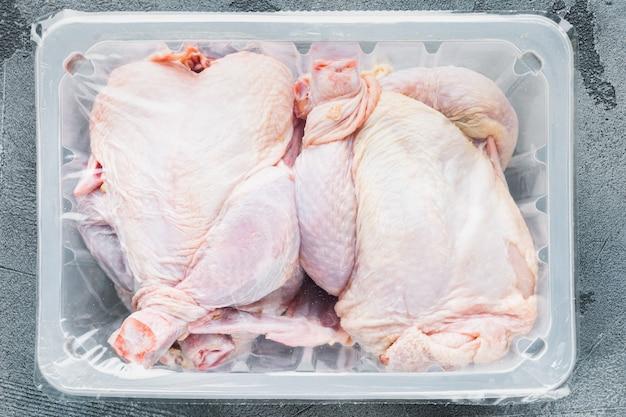 Сырая курица в пластиковом вакуумном лотке, на сером фоне, вид сверху