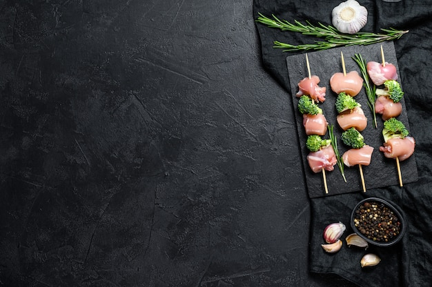 Raw chicken shish kebab with broccoli,  barbecue. black wall. top view. space for text